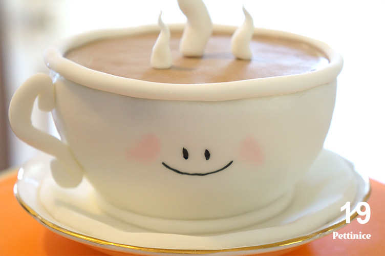 19. Use edible glue to adhere the tea cup handle. (Royal Icing or melted chocolate can also be used for this step). Use edible marker to draw a smiley face on the tea cup, draw the two eyes and the mouth. Pink petal dust can be lightly brushed on to give the effect of rosy cheeks.