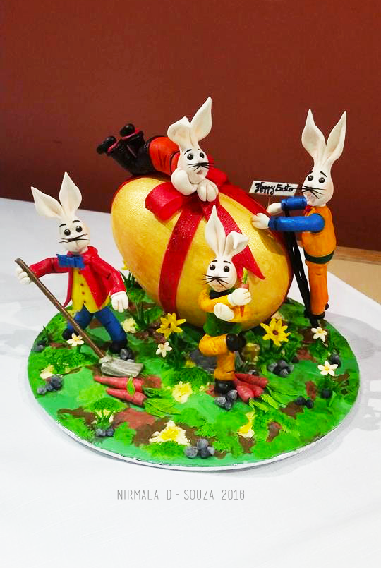 Easter Bunnies decorating large gold egg cake by Nirmala D Souzav