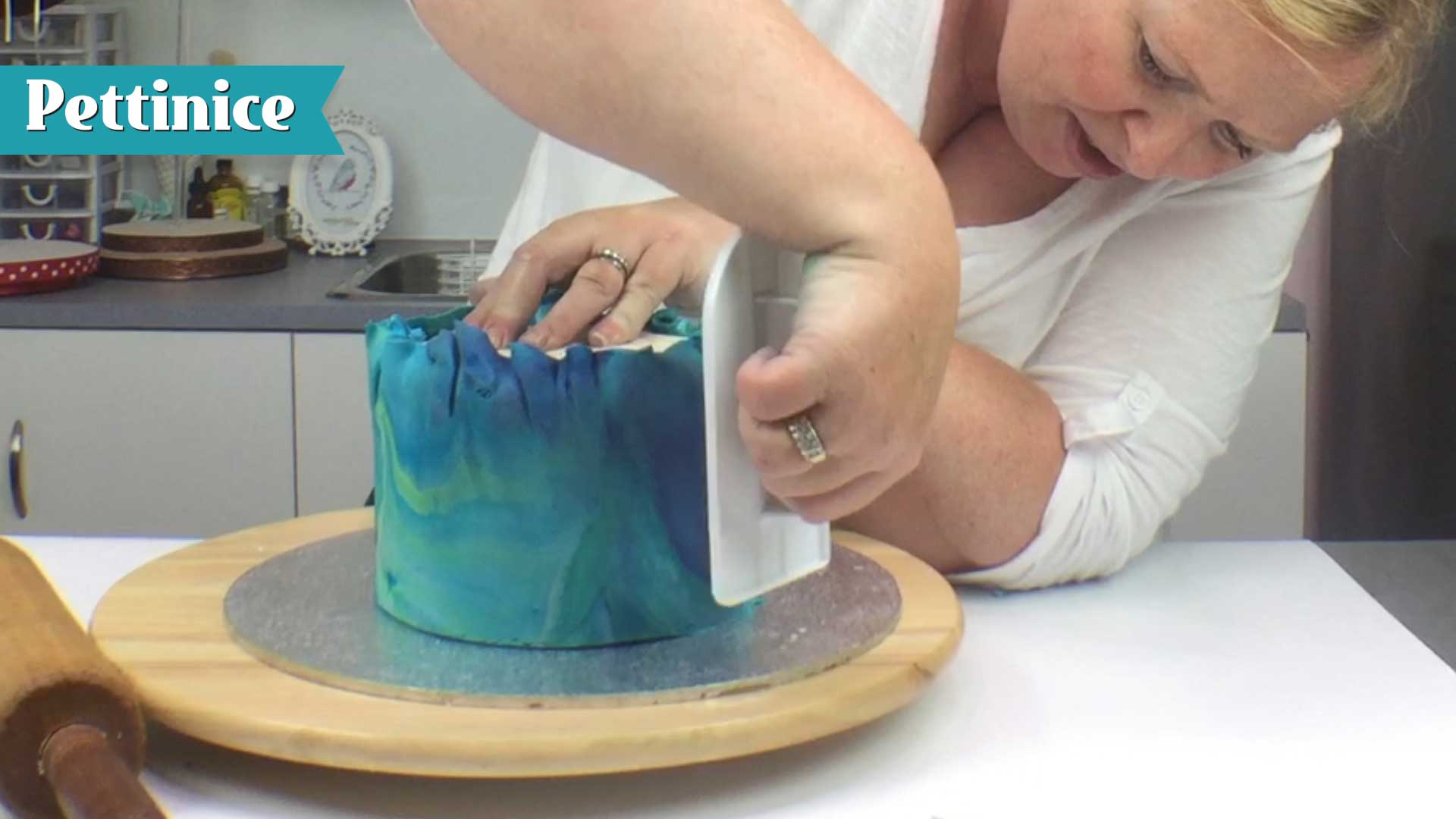 Use your cake smoother to push fondant to the board, working your way around the cake.  You will trim off the excess next.  We will demonstrative removing the folds shown here.  Because we used Sprink, it allows us more working time with our fondant.