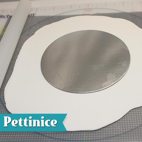 Roll out  Pettinice larger than the size of the presentation board. Place a board the same size as your cake in the centre.
