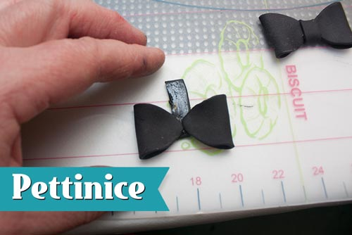 Cut strips of black fondant about 3cm long by about 3/4cm wide. Brush glue along strip and place the folded ovals opposite each other as shown.  Fold the strip over and secure it, hiding seams at the back.