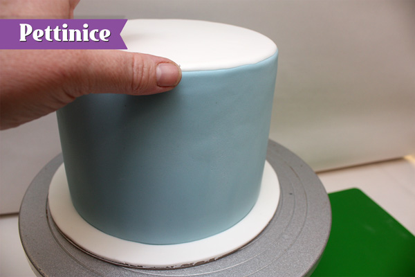Attach the circle of white fondant using water on top of the cake covered with the blue fondant.