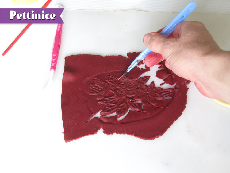 Using your scapel or sharp tool, cut around the lace.