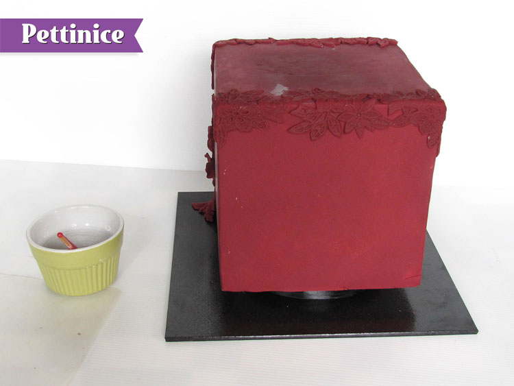 Using your water or sugar glue attach the three pieces to the top edge of the cake