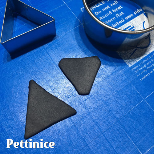 Roll out some thin Black Pettinice, get a triangle cutter and a circle cutter, round the edges of your triangles and place them on ALL the corners of the Amp.