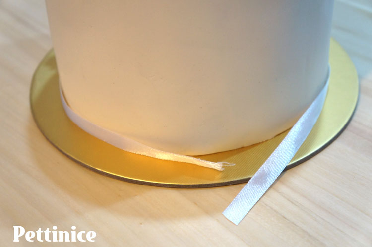 Have your ribbon overlap and fix seams to the back of the cake.