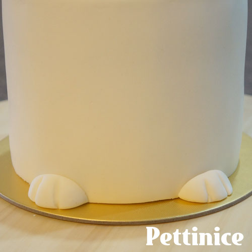 Using a little bit of water, stick the paws to the front of the cake.