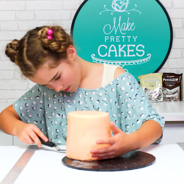 You could remove the fondant at the top, but we decided not to.  Nudge your cake to the edge so you can slip your spatula under the cake....