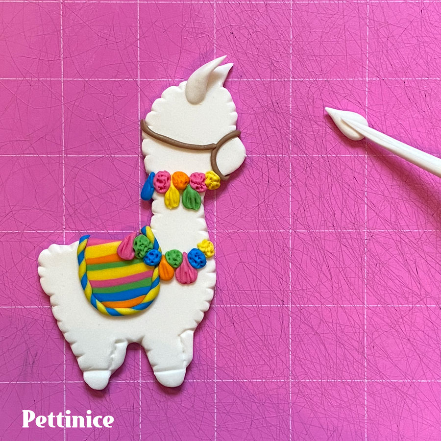 For the other ear, make a wee tear drop shape and press the quilting tool on the centre to make it more ear shaped, pinch at the base, and stick to the llama just behind the cut out ear.