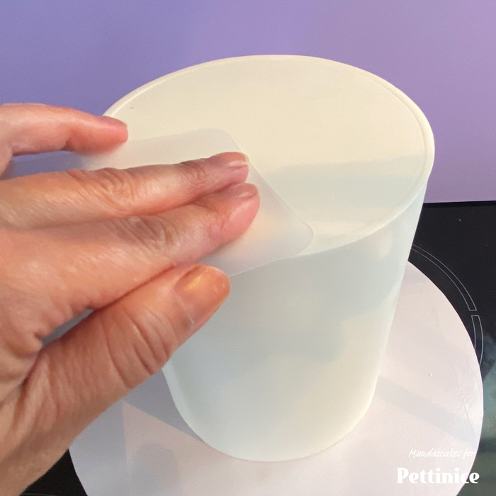 Put a cake board on the base of the cake and flip it back to being right side up. There will be a seam, which you can smooth out a bit more using a smoother or flexi smoother.